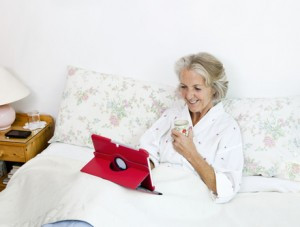 © Photographerlondon | Dreamstime.com - Happy Senior Woman Using Digital Tablet While Having Coffee On Bed At Home Photo