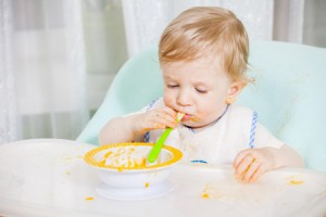 bambino-pappa-seggiolone-©-Liandstudio-_-Dreamstime.com---Smiling-Baby-Eating-Food-On-Kitchen-Photo