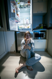 spuntino-notturno-mezzanotte-Kryzhov | Dreamstime.com - Woman Sitting Near Refrigerator At Late Night Photo