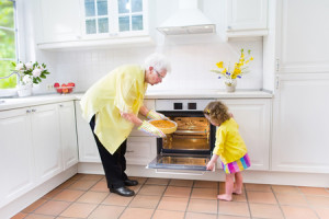 nonna-nipotina-cucina-forno_Famveldman-_-Dreamstime.com---Grandmother-and-sweet-girl-baking-pie-in-white-kitchen